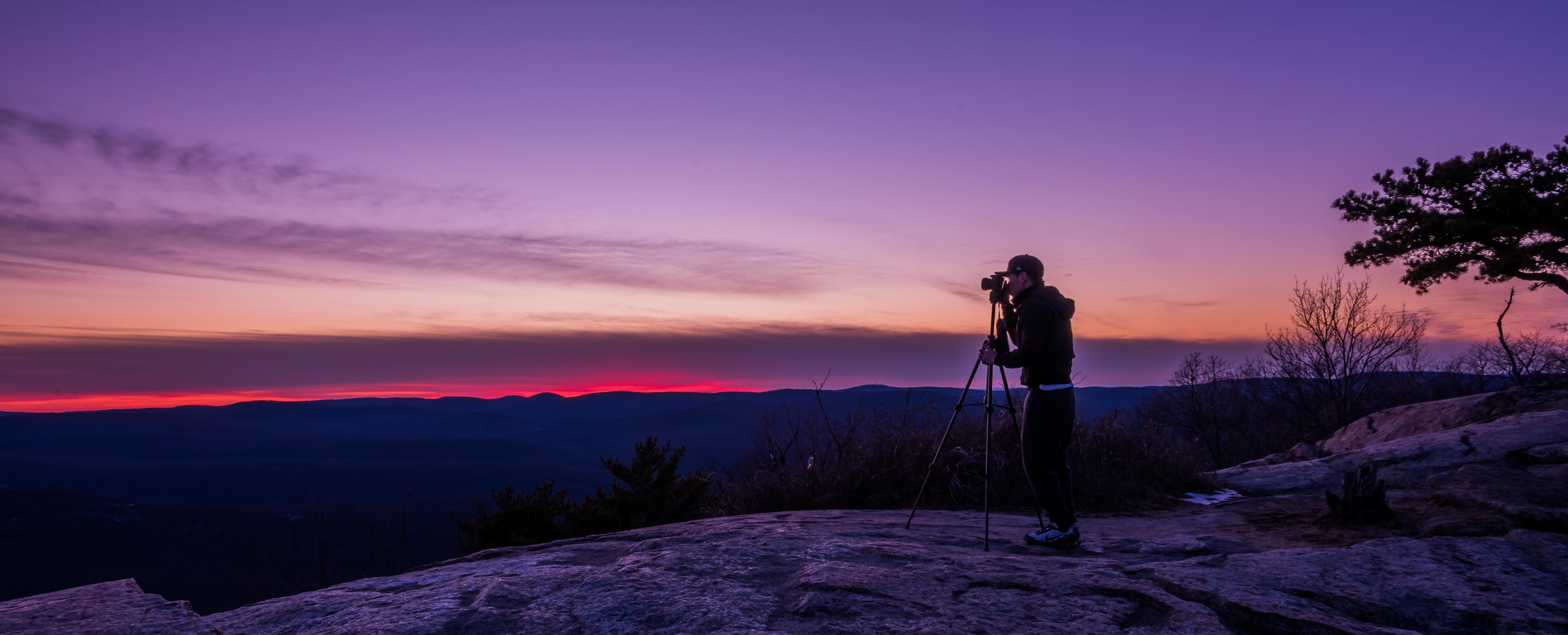 man using tripod for photography at sunset